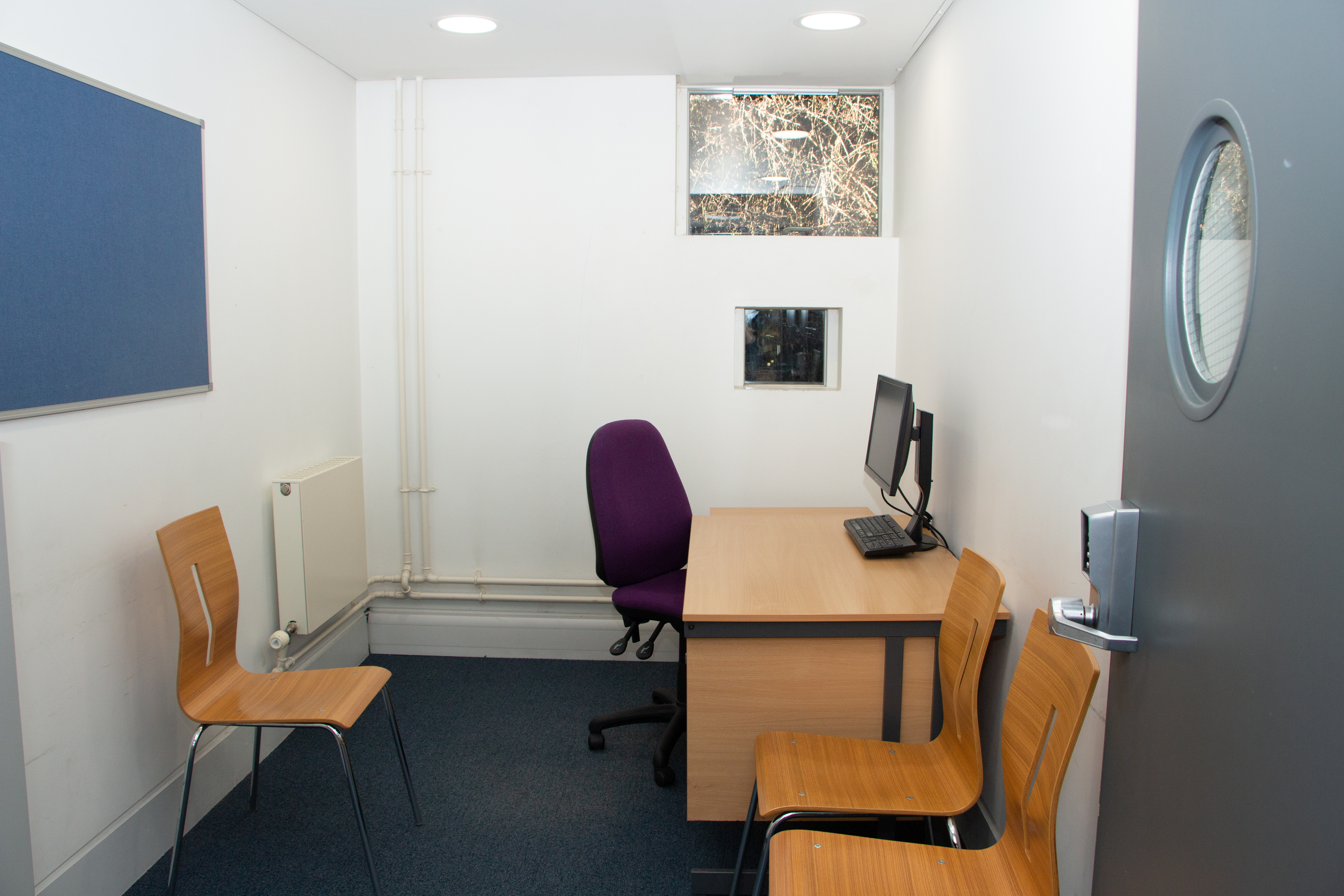 Small room with four chairs and desk