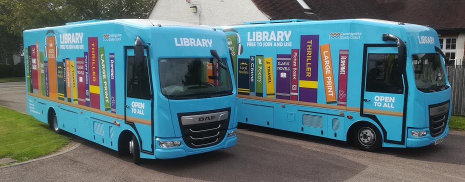 Two blue mobile libraries, painted with images of books on the side