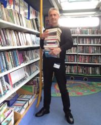 David Hamilton standing in front of library shelves, holding books