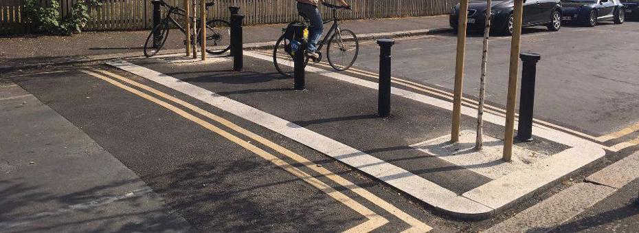 Raised bollards preventing cars entering road but allowing cyclists and pedestrians