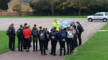 Students standing around a road safety officer and car