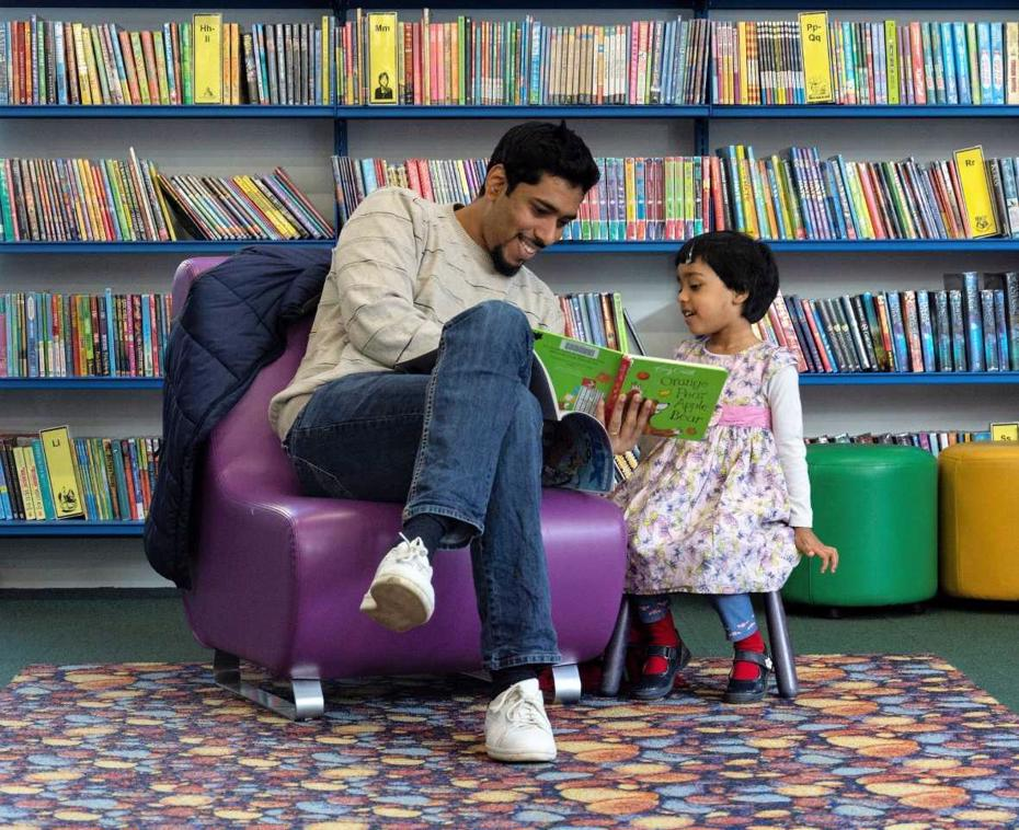 Parent or carer reading with their child in a library