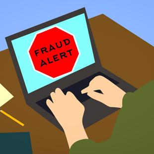 Person sitting at laptop with a fraud alert notice on screen